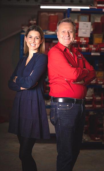 Vater und Tochter in einer Werkstatt lachen freundlich in die Kamera